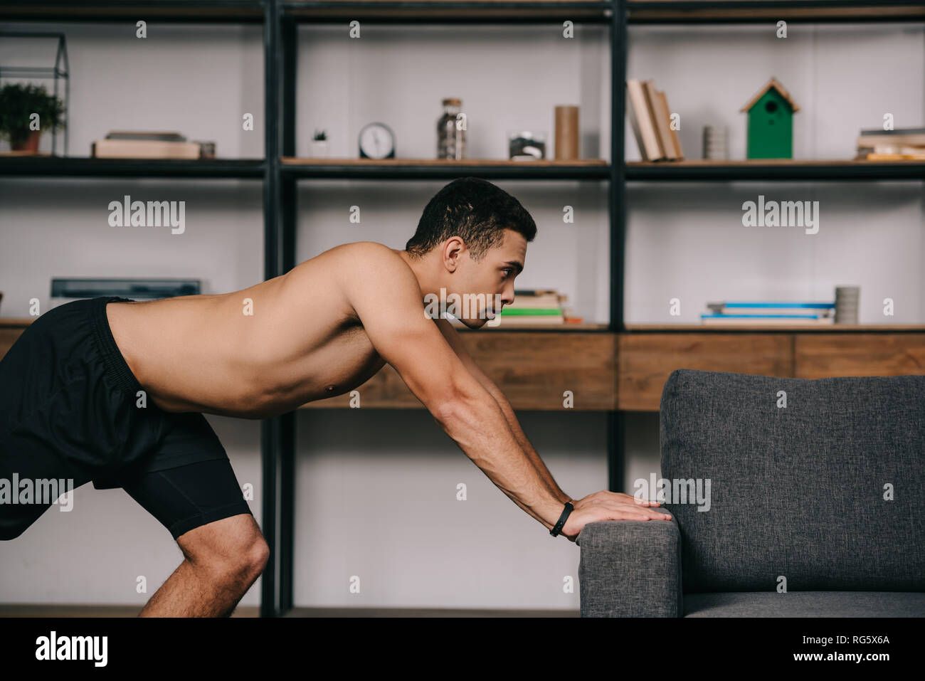 Sofa Workout Strong Mixed Race Man Workout Near Sofa In Living Room Stock Photo