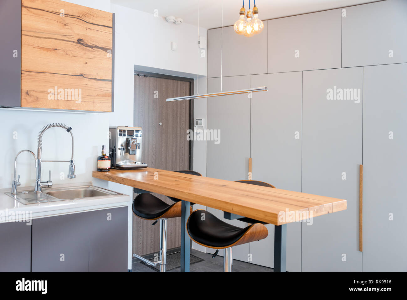 Modern Kitchen Interior With Lights On Brown Wooden Table And Bar Stools Coffee Machine Contemporary Interior With Loft Elements Stock Photo Alamy
