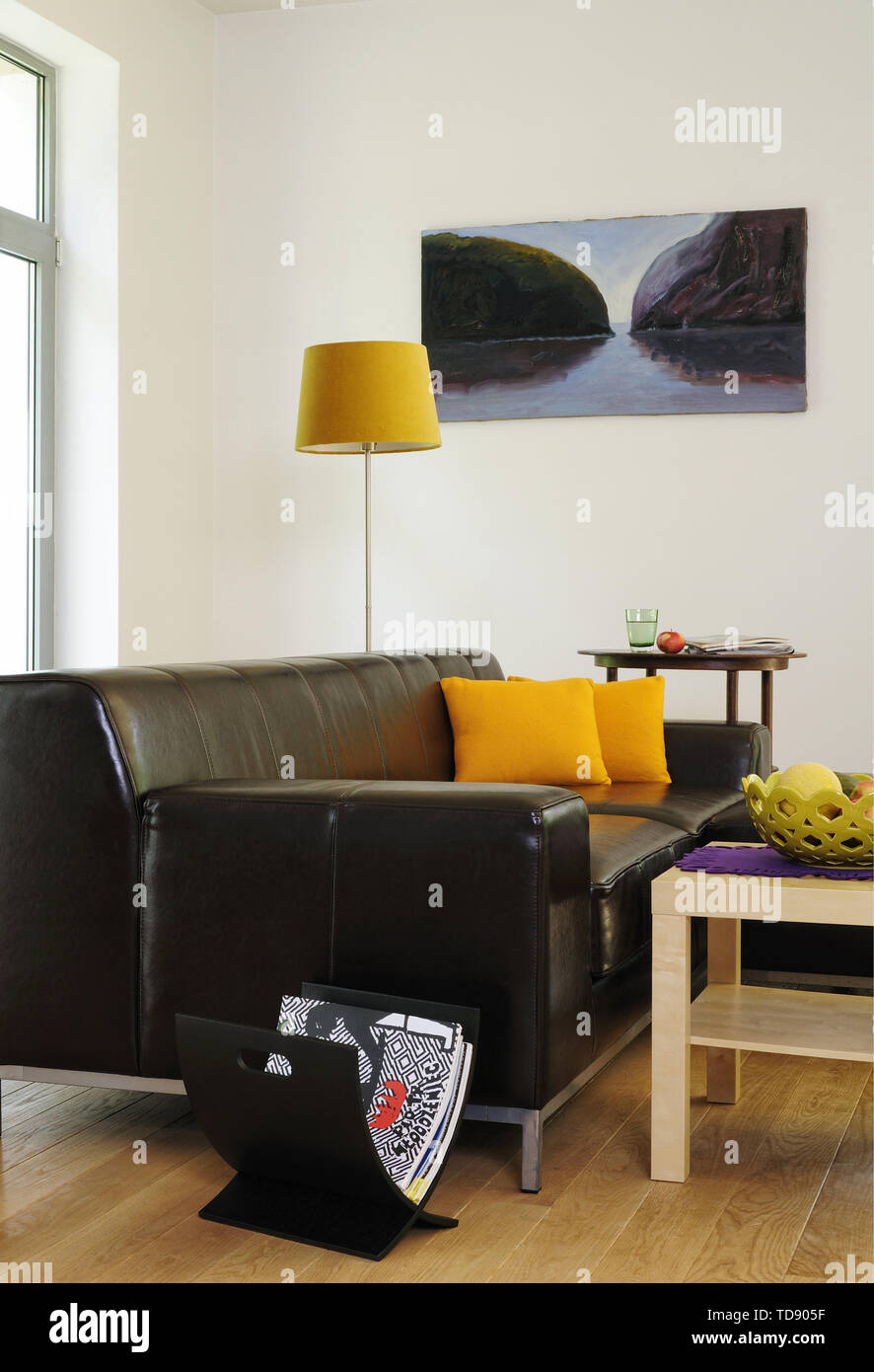 Yellow Cushions On Black Leather Sofa In Modern Sitting Room Uk Irish Use Only Stock Photo Alamy