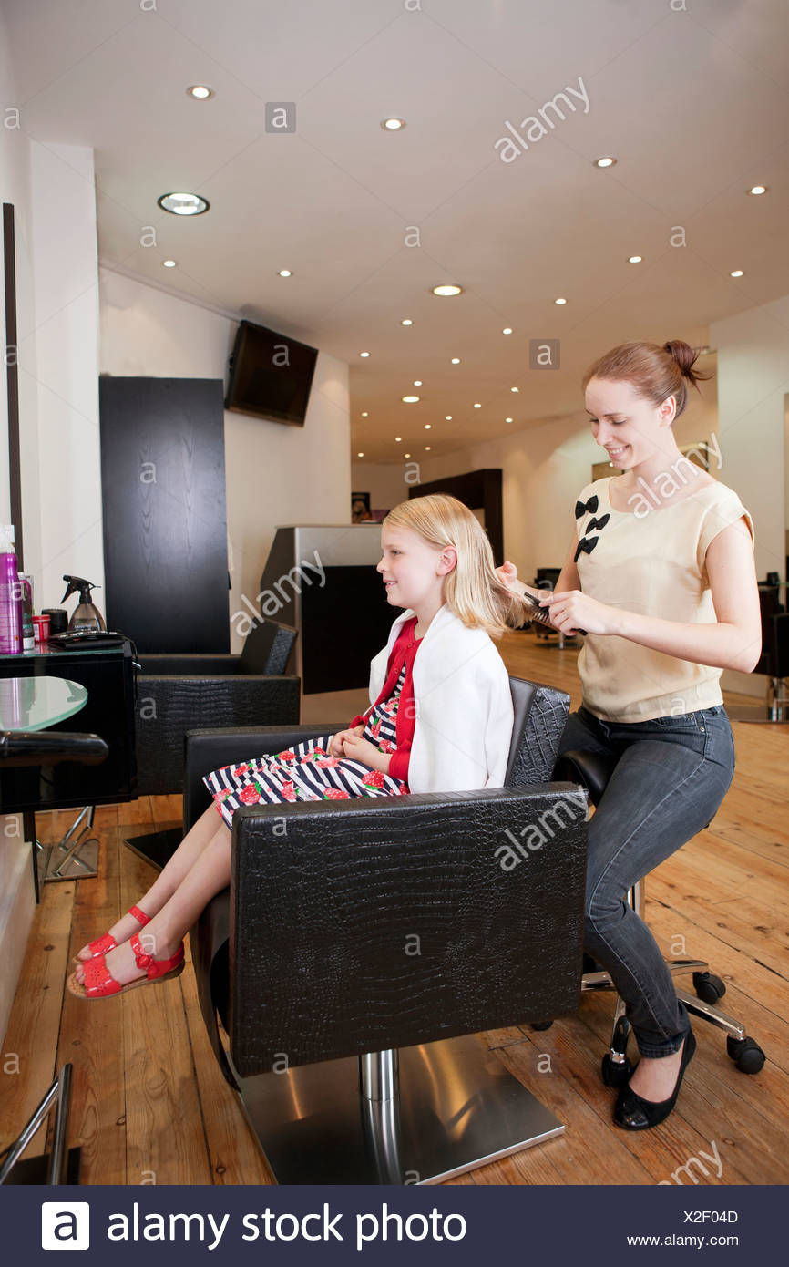 Hairdressing Salon A Female Hairdresser Brushing A Young Girls Hair In A Hairdressing