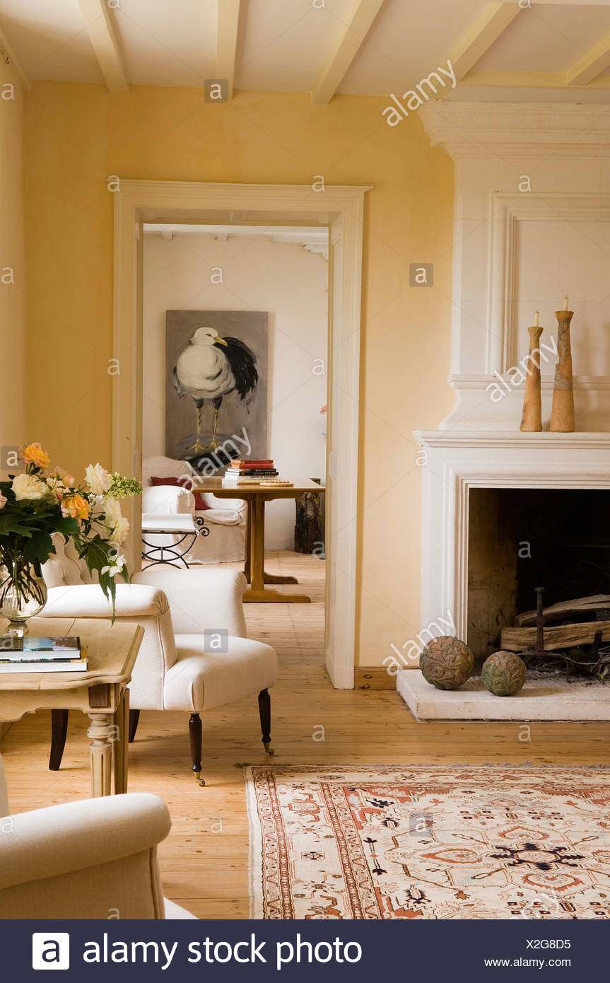 French Country Fireplace Cream Upholstered Armchair Beside Fireplace In French Country
