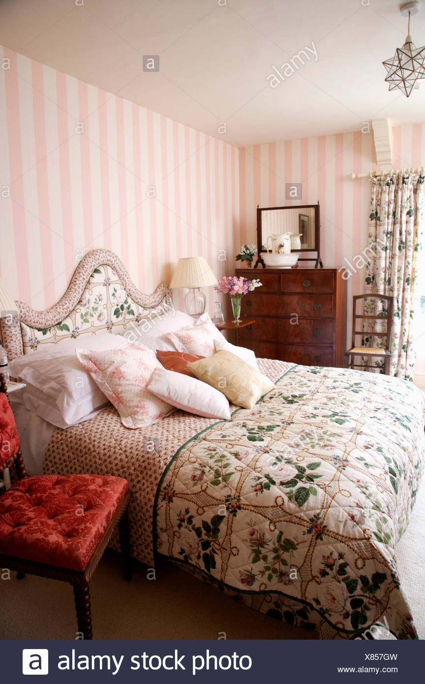 Pink Striped Wallpaper In Country Bedroom With Floral Quilt And Matching Headboard On Bed Stock Photo Alamy
