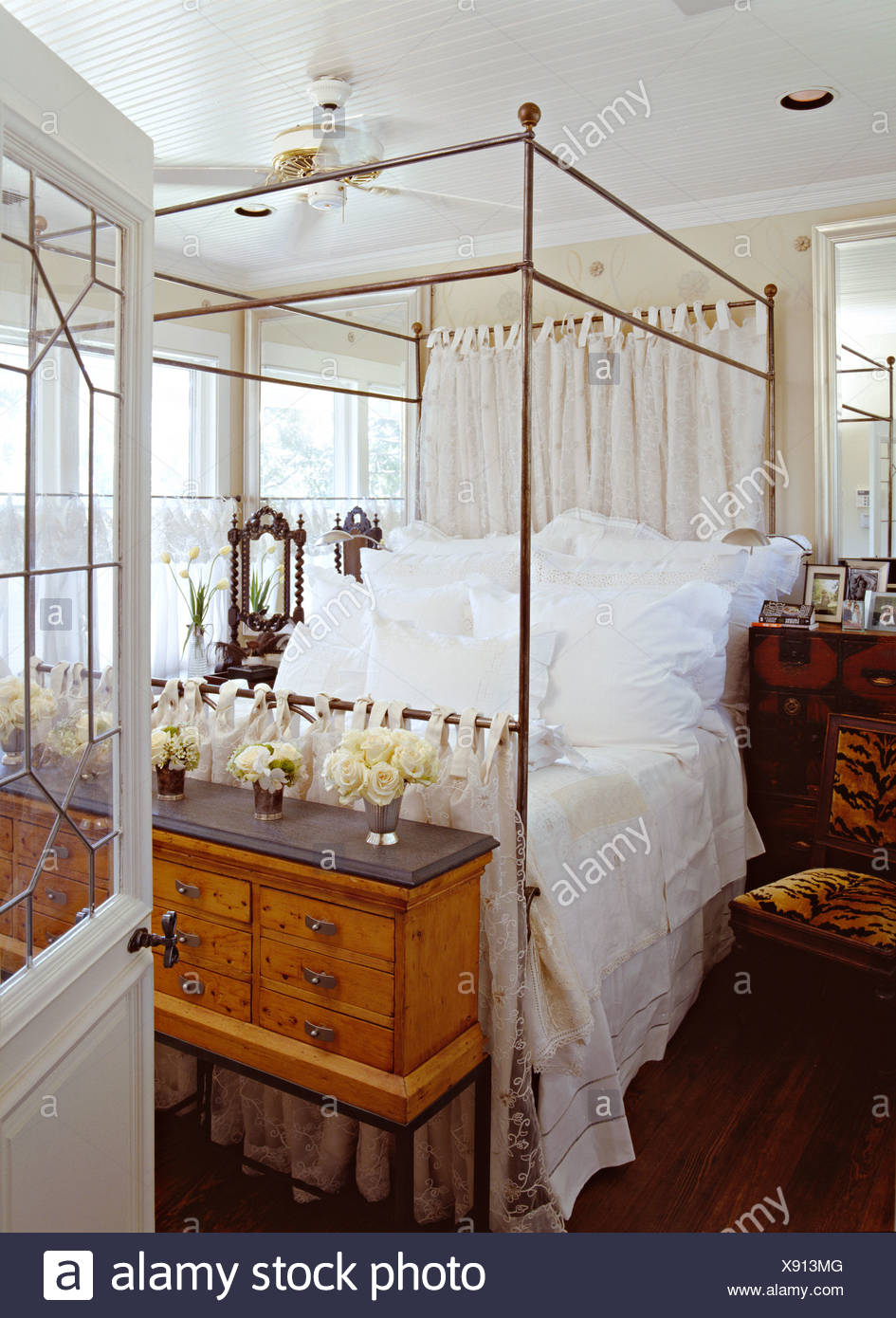Single Four Poster Bed White Roses In Single Vases On Small Chest Below Metal Fourposter