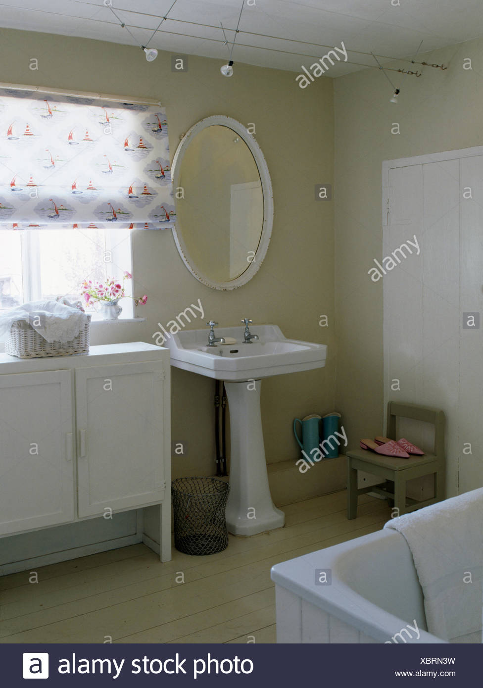 Oval Mirror Above White Pedestal Basin In Country Bathroom With Patterned White Blind On Window Above Painted Cupboard Stock Photo Alamy
