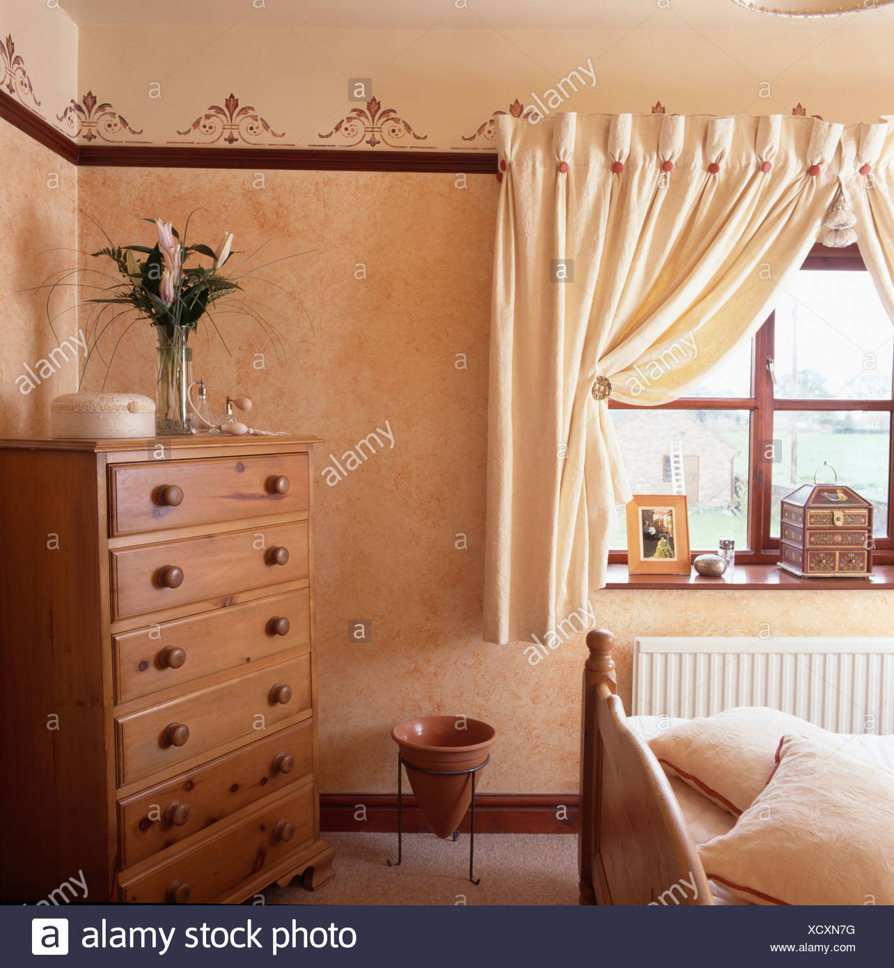 Chest Of Drawers In Corner Of Small Bedroom With Cream Curtains At Window And Stenciled Border On Walls Stock Photo Alamy