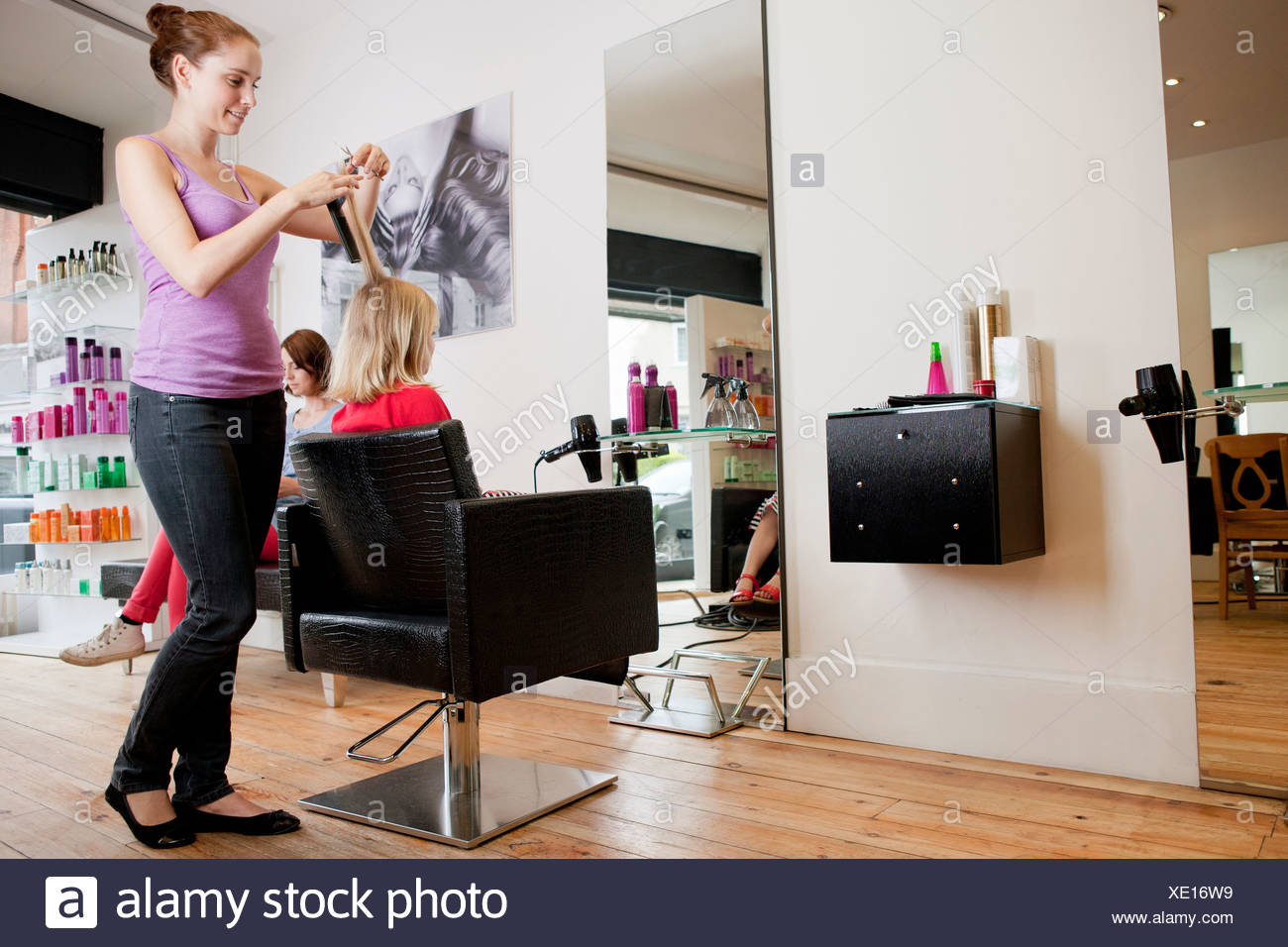 Hairdressing Salon A Female Hairdresser Cutting A Young Girls Hair In A Hairdressing