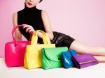 Woman with many colorful bags and purses. Isolated on cute pink color.