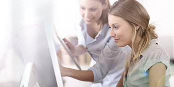 Young women in office working together on desktop
