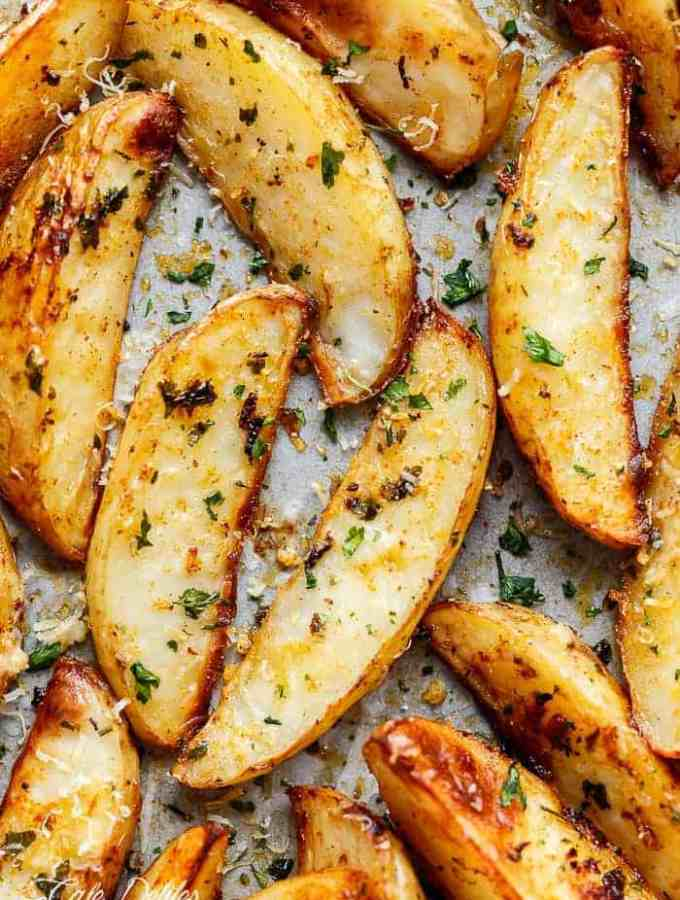 Crispy Garlic Baked Potato Wedges are soft pillows on the inside, and crunchy on the outside with a good kick of garlic and parmesan cheese! | http://cafedelites.com