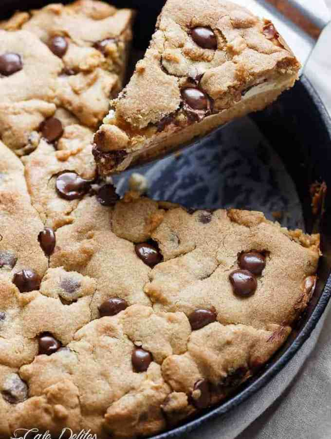 A crispy, soft Cheesecake Stuffed Chocolate Chip Skillet Cookie! Layers of cookie dough and cheesecake is the ultimate dessert for cheesecake/cookie lovers!   http://cafedelites.com