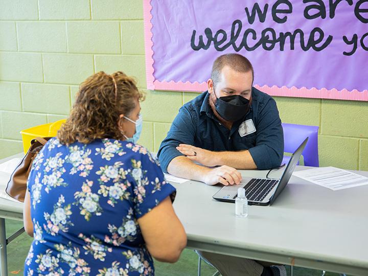 一个戴着面具的男人在帮助一个坐着的女人处理文书工作