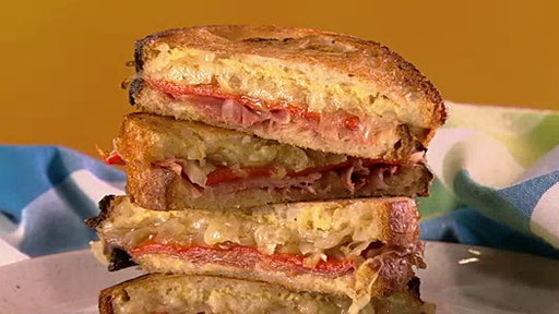 "Chef Mario Batali and chef Michael Symon show us how to make a delicious grilled cheese Espanol and late night Salami sandwich on the Thursday, May 6, 2015 episode of ""The Chew""!"
