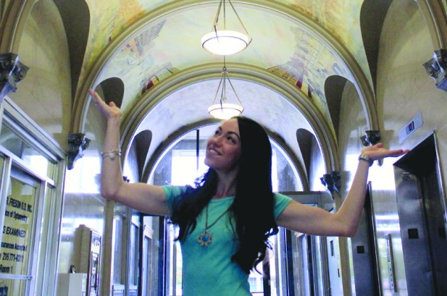 Jessica Newell stands below her Cleveland-themed mural in the lobby of the United Bank Building, which is now home to Skylight Financial Group, in Cleveland's Ohio City neighborhood.
