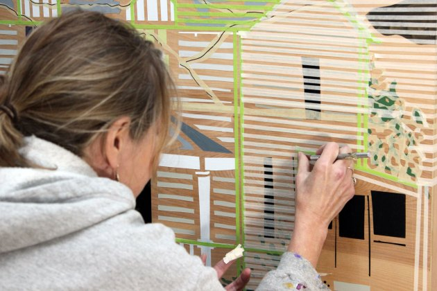 "Cooper applies with precision strips of masking tape to a piece she's working on that depicts the house in ""The Waltons."""