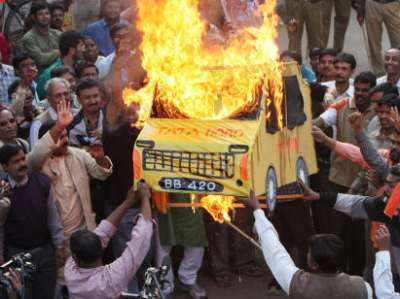 Activists of the Trinamool Congress-led 'Krishi Jami Raksha Committee' (KJRC) burn an effigy of the Tata Motors' ambitious people's car 'Nano' during a demonstration in Singur, where construction of the Nano car factory is in process, some 30 kms north of Kolkata, 10 January 2008. India's giant Tata Group 10 January unveiled a USD 2,500 car it bills as the world's cheapest amid predictions the compact, no-frills vehicle could revolutionise how the nation of 1.1 billion people travels.    AFP PHOTO/STR (Photo credit should read STRDEL/AFP/Getty Images) (Newscom TagID: afplivetwo323838)     [Photo via Newscom]