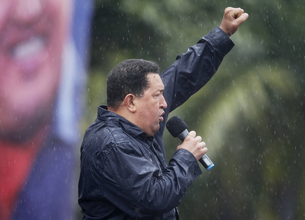 Venezuela's President and presidential candidate Chavez raises his arm as he delivers a speech under the rain during his closing campaign rally in Caracas
