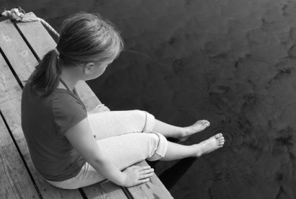 Young girl dipping feet in the lake from the edge of a wooden boat dock