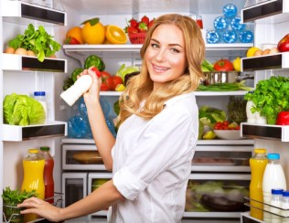 Woman chosen milk in opened refrigerator, cool new friedge full of tasty organic nutrition, female preparing to cook, healthy eating concept