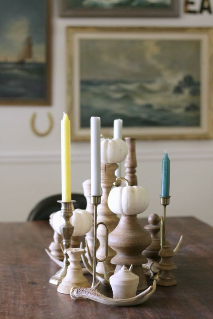 Fall Centerpiece with white pumpkins, blue and green candles, brass candlesticks, and stripped wood pieces.
