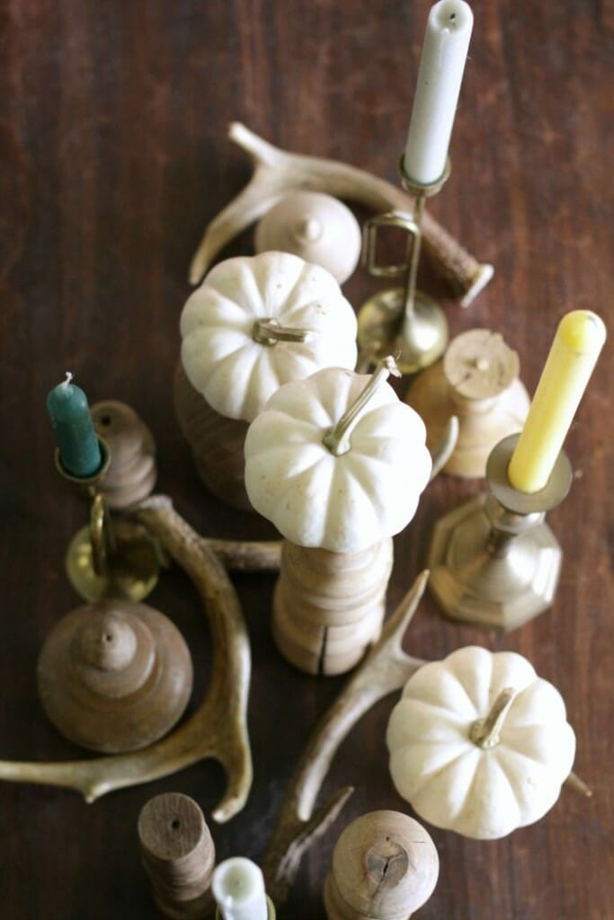 Aerial view of Fall centerpiece with white pumpkins, brass candlesticks, blue and green candles, and stripped wood