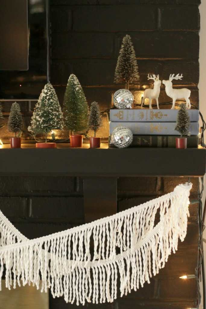Eclectic Black Christmas mantle with vintage books, deer, and bottle brush trees