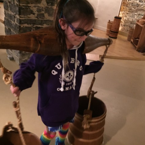 my daughter trying on a reproduction of an old shoulder yoke for carrying water