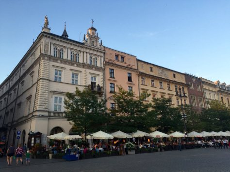 the Main Square in Krakow is surrounded by beautiful buildings, most of which house restaurants or cafes on the ground floor