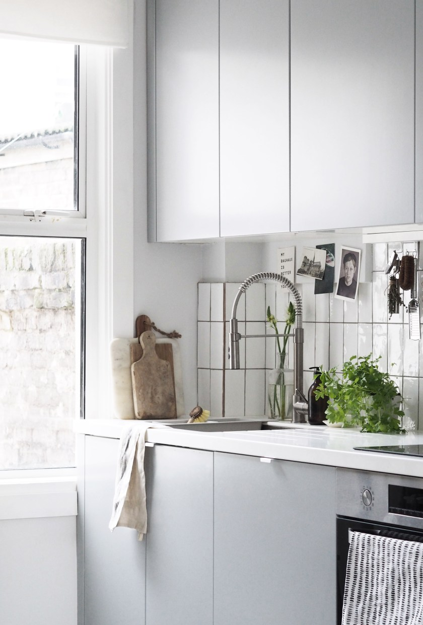 AFTER: Minimal grey units and white metro tiles create a calm, relaxed space, a world away from the dark, yellow kitchen before