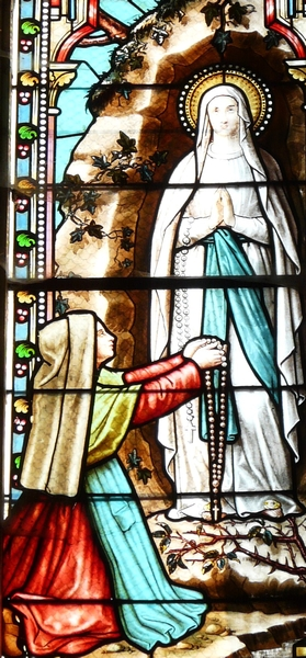 detail of a stained glass window depicting the apparition of the Virgin Mary to Bernadette Soubirous; date and artist unknown; church of Saint-Pierre-ès-Liens, Bourdeilles, Dordogne, France; photographed on 17 December 2009 by Père Igor; swiped from Wikimedia Commons