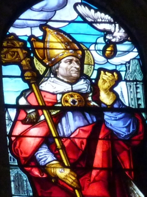 detail of a stained glass window in the cathedral of Our Lady of the Assumption, Segovia Spain, depicting Saint Remegius of Rheims receiving a lamp from a dove; date and artist unknown; photographed on 22 Juuly 2013 by GFreihalter; swiped from Wikimedia Commons