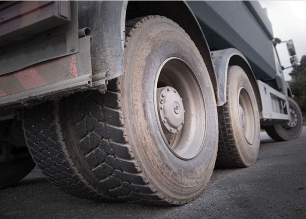 A dump truck's axle and tires flew off of the truck and struck an on-coming car.