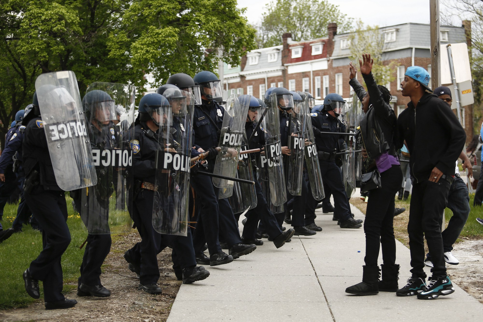 A baltimore police officers in riot gear push protestors back along reisterstown road near mondawmin mall april 27 in baltimore maryland