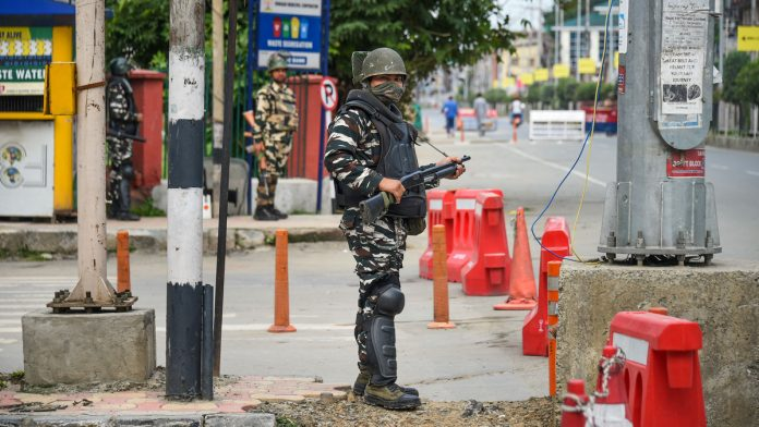 Security personnel stand guard during restrictions in Srinagar