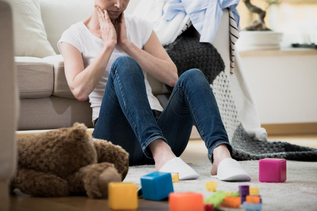 Stressed parent sitting amongst scattered toys.
