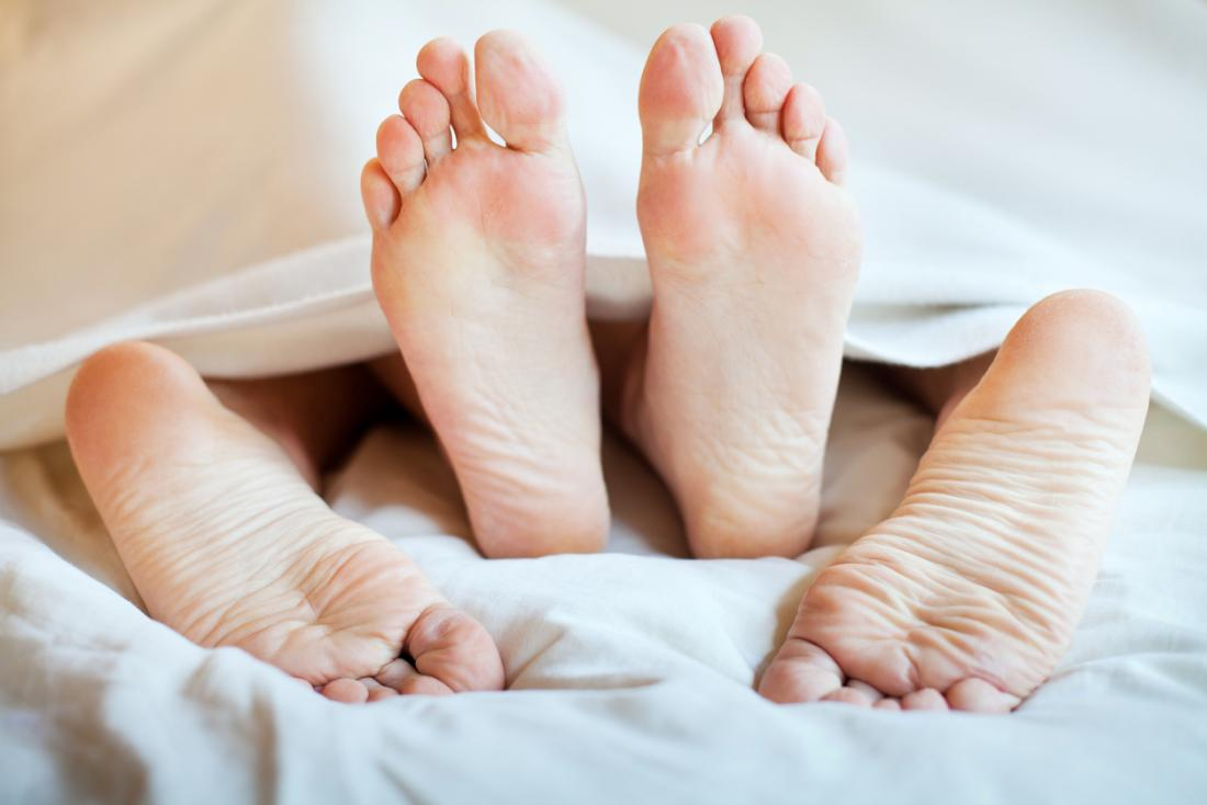 couple's feet under bed sheets