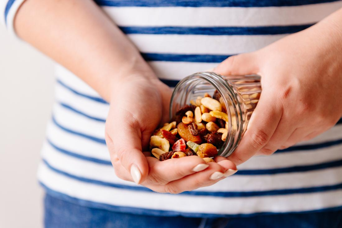 woman pouring nuts and dried fruit into hand