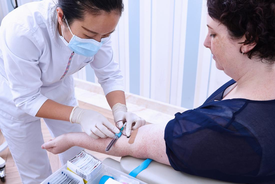 Woman having blood sample drawn from arm for testing