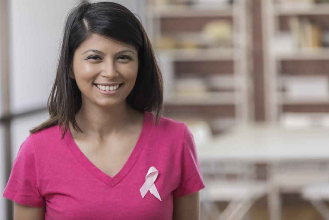 woman wearing breast cancer ribbon smiling at camera
