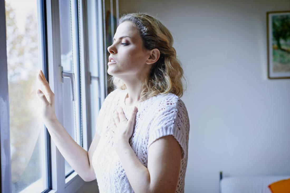 Woman with shortness of breath holding chest in pain looking out of window