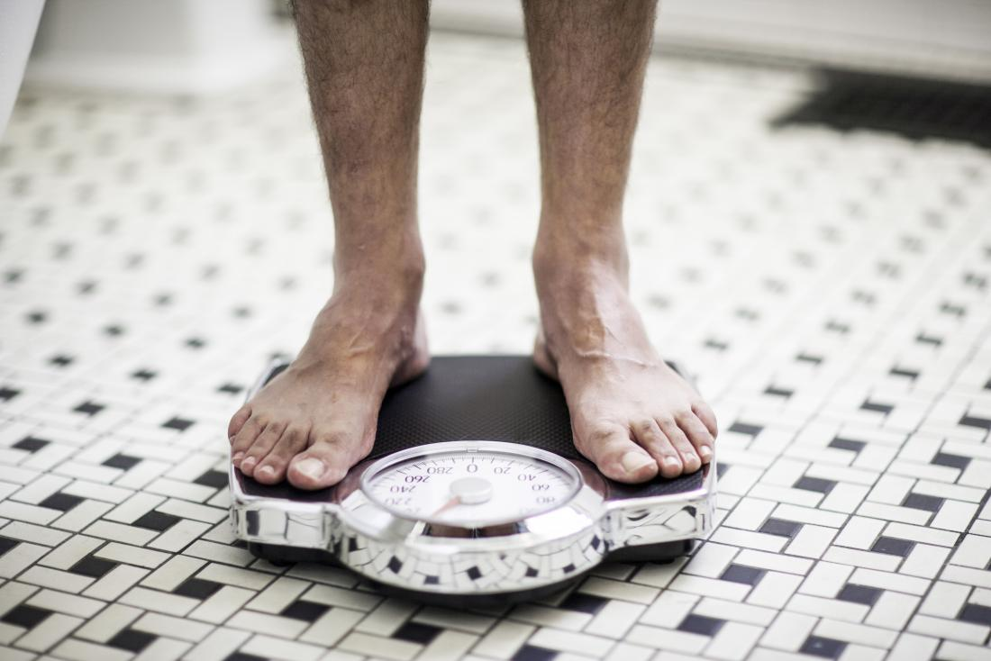 Male feet standing on scales to check for weight loss alongside blood in the urine.