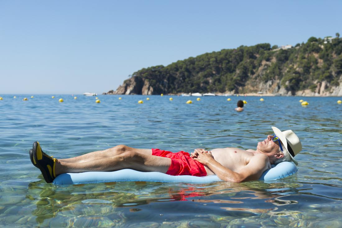 an older man lying on a lido in the sea.