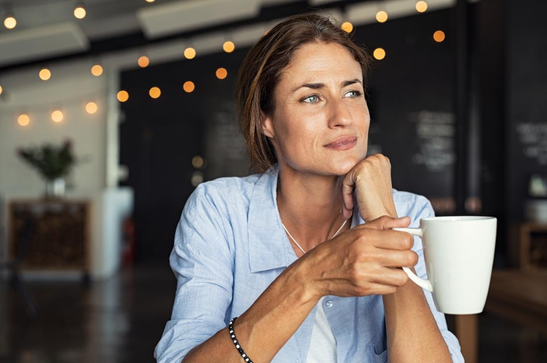 a woman drinking coffee with a faint smile.