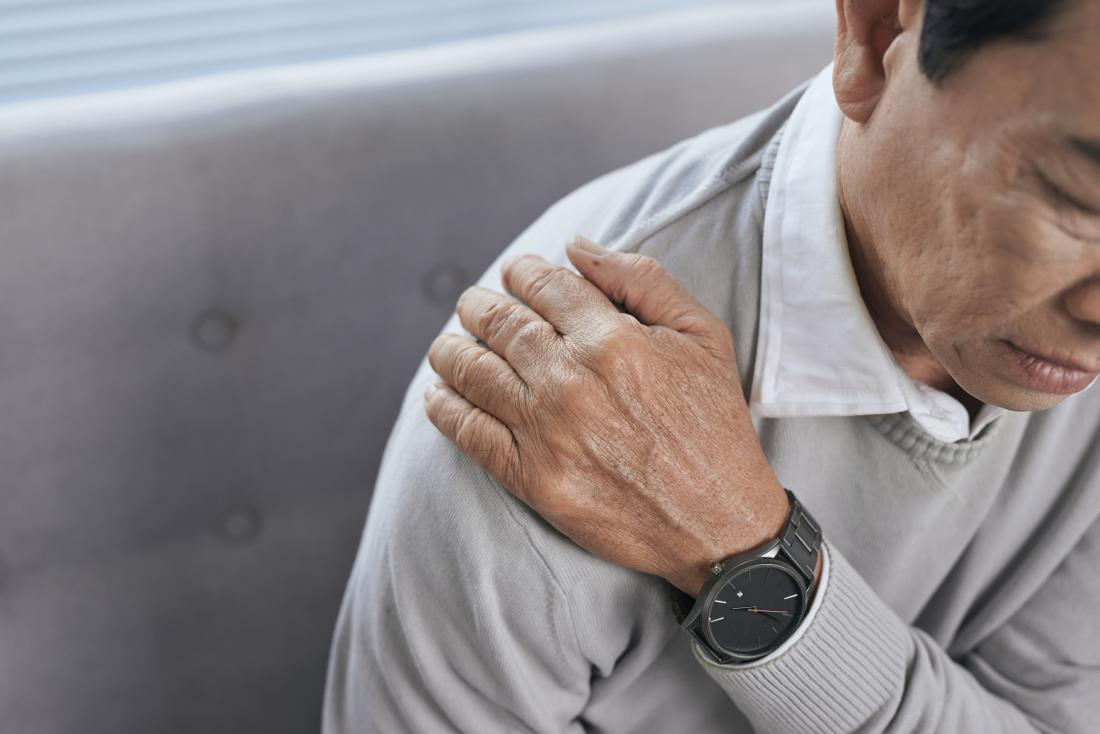 senior man holding shoulder because of joint pain