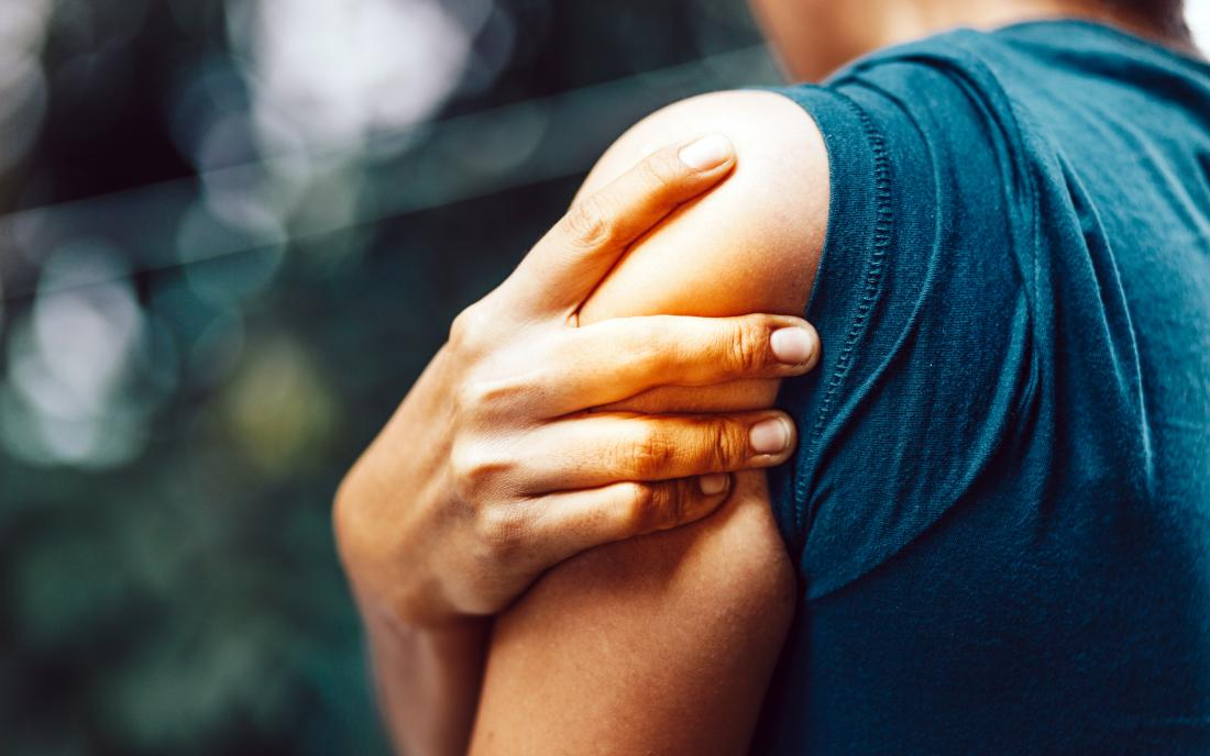 a woman with a pain in her shoulder due to a Shoulder impingement