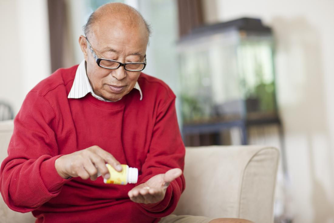 older man taking medication
