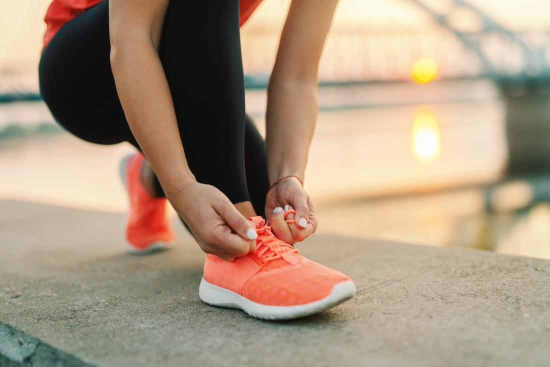close up of woman tying her running shoes