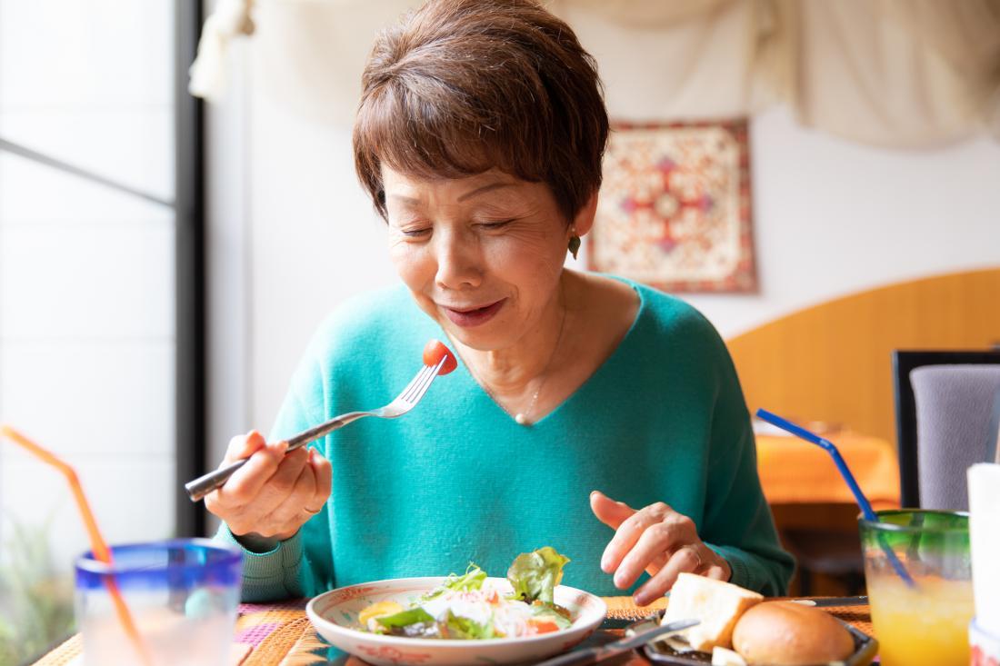 senior woman eating vegetables