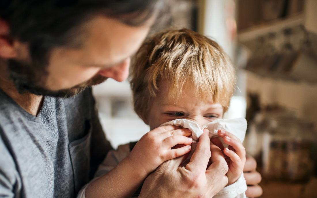 a dad blowing the nose of his toddler who is showing symptoms of the flu.