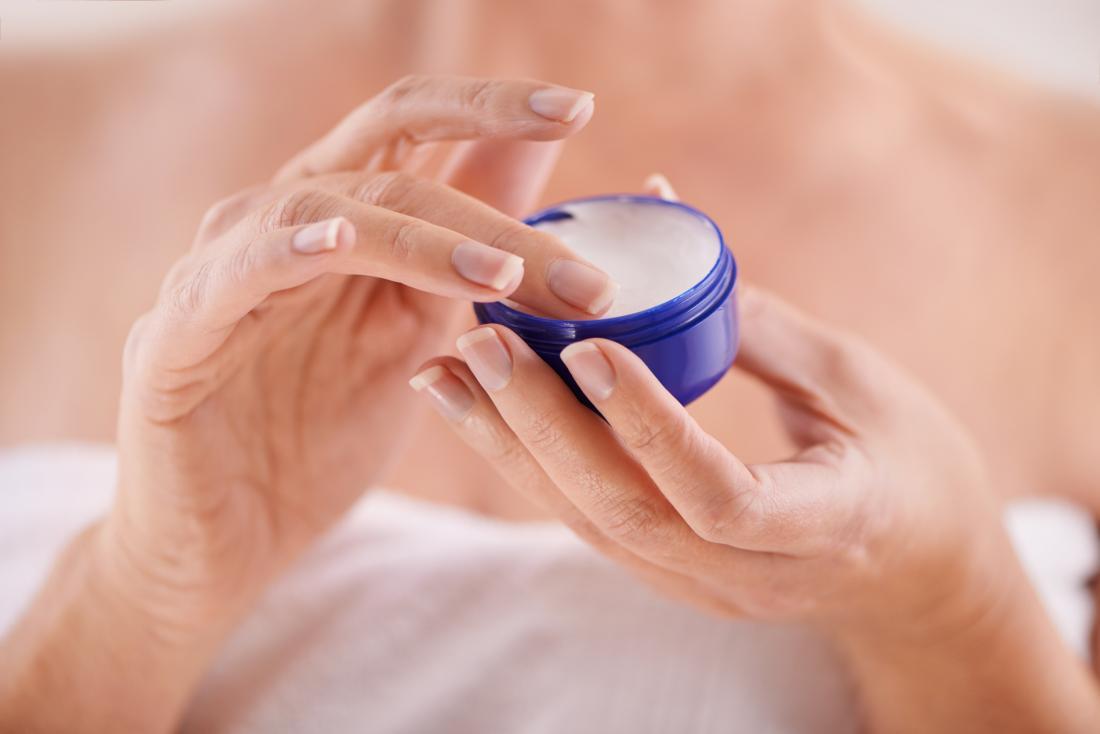 woman's hands applying cream