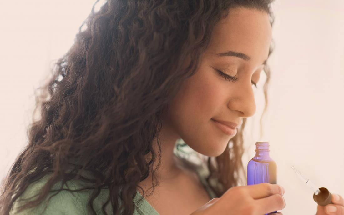 a woman smelling neem oil that she is going to use for her skin